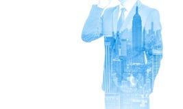 商人两次曝光有手机和城市大厦背景 抽象设计想法 免版税库存图片