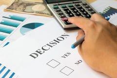 商人为关于文件的决定计算与计算器 免版税库存照片