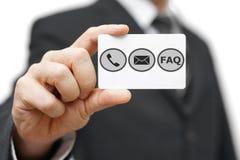 商人举行与电话、电子邮件和常见问题解答象的名片 免版税库存图片