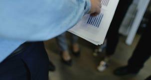 商人举行与财务图,小组的报告文件商人谈论财政图表数据在期间 股票录像