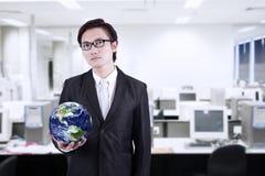 商人举行地球在办公室 库存图片