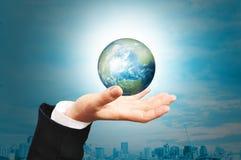 商人举行地球地球的手 免版税库存照片