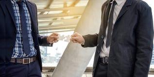 商人举行彼此的七巧板 企业teamwor 免版税图库摄影
