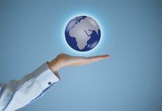 商人举行或拿着世界地球手中 库存照片