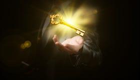 商人举行金子光亮的钥匙,企业概念 免版税图库摄影