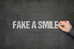 商人伪造品在黑板的微笑 库存图片