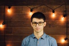 年轻商人佩带的玻璃,看在木背景墙壁上的照相机有拷贝空间的 库存照片
