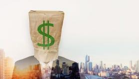 商人佩带被弄皱的包装纸袋子,与绿色美元的符号的和在日出的两次曝光都市风景 图库摄影