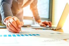 商人使用一台膝上型计算机并且使用笔分析数据fr 免版税图库摄影