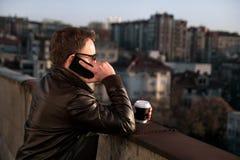 商人使用在屋顶和饮用的咖啡的callphone 免版税库存图片