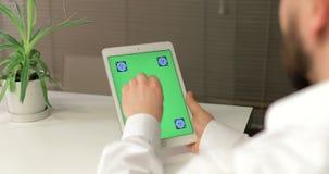 商人使用有绿色屏幕的片剂计算机,他猛击和触摸屏 办公室是明亮和现代的 影视素材