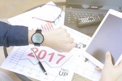 商人使用片剂的和膝上型计算机为与smartwatch的分析财政图表显示遇见当前日程表的通知 免版税库存图片