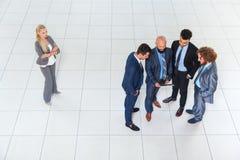 商人使用片剂计算机,一起商人公共的小组讨论会议,在旁边女实业家立场 免版税库存图片