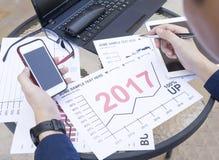 商人使用膝上型计算机的和智能手机和片剂分析财政图表年2017趋向计划室外pla的预测 免版税库存图片