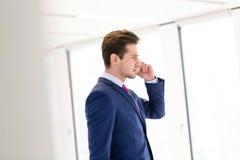 年轻商人侧视图使用手机的在新的办公室 库存图片