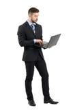 年轻商人侧视图在衣服的使用膝上型计算机 图库摄影