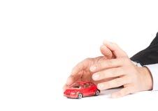 商人保护用他的手一辆红色汽车,汽车保险概念 库存照片