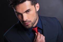 商人修理他的领带 免版税库存图片