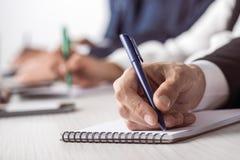 商人候宰栏和文字在笔记本,当坐在桌上时 免版税库存图片