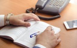 商人做在一本膨胀的书的笔记 仅在框架现有量 免版税图库摄影