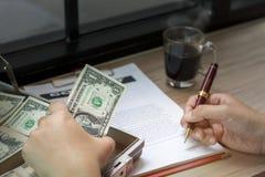 商人写商业文件的候宰栏的手 免版税库存图片