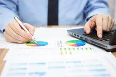 商人分析企业数据并且使用膝上型计算机 免版税库存图片