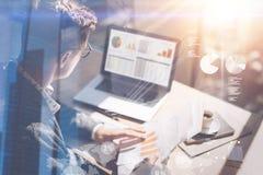年轻商人分析关于笔记本屏幕的库存报告 数字式屏幕,虚拟连接象,图的概念 库存照片