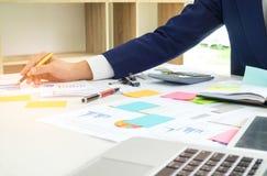 商人分析图表数据并且采取关于轻碰的笔记 免版税库存照片