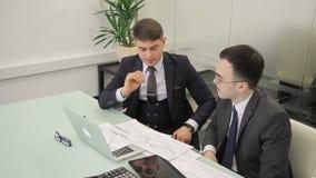 商人劝告关于财务分析的客户在书桌 股票录像