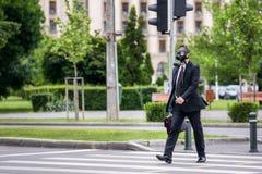 商人十字架室外的街道戴着在面孔的一个防毒面具 免版税库存图片