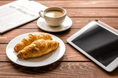 商人午餐在家用咖啡, croisant和设备 免版税库存图片