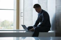 商人单独坐与膝上型计算机的一条长凳 免版税库存照片