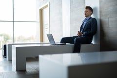 商人单独坐与膝上型计算机的一条长凳 库存图片