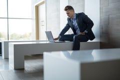 商人单独坐与膝上型计算机的一条长凳 免版税库存图片