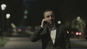 商人友好谈话由电话在好心情的城市公园 图库摄影
