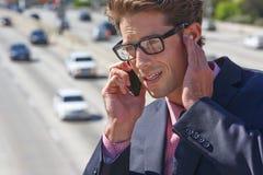 商人发表演讲关于手机由喧闹的高速公路 免版税库存图片