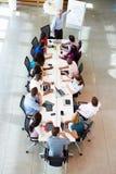 商人发言在会议室表附近 免版税库存图片