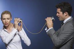商人叫喊对同事通过锡罐电话 免版税图库摄影
