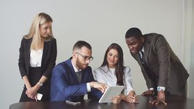 商人召开并且开一起看关于数字式片剂的非正式会议数据 免版税库存照片