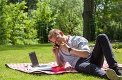 商人吃三明治和谈话在电话 免版税图库摄影