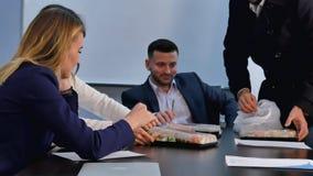 年轻商人吃午餐一起在办公室 免版税库存照片