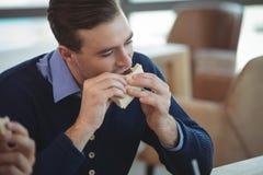 商人吃早餐在办公室自助食堂 免版税库存照片