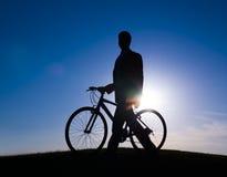 商人和一辆自行车在小山 免版税库存照片