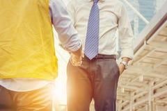 商人和企业工程学握手在城市背景 库存图片
