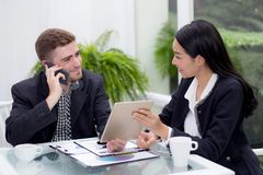 商人和做会议和看片剂的妇女人为分析行销 免版税库存图片