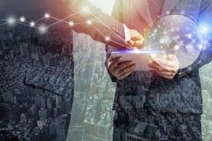 商人和城市两次曝光,计划在智能手机和片剂有秘书和女实业家的关于项目和fina 库存照片