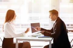 商人和女商人签合同 对贷款期间妇女唱歌合同满意,当坐在前面o时的书桌 免版税库存图片