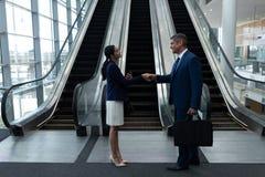 商人和女实业家与彼此握手在自动扶梯附近 免版税库存照片