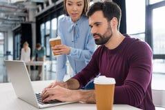 商人和女实业家与膝上型计算机一起使用在小企业办公室 免版税库存图片