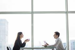商人和女实业家会议在面对面现代的办公室谈论计划 免版税图库摄影